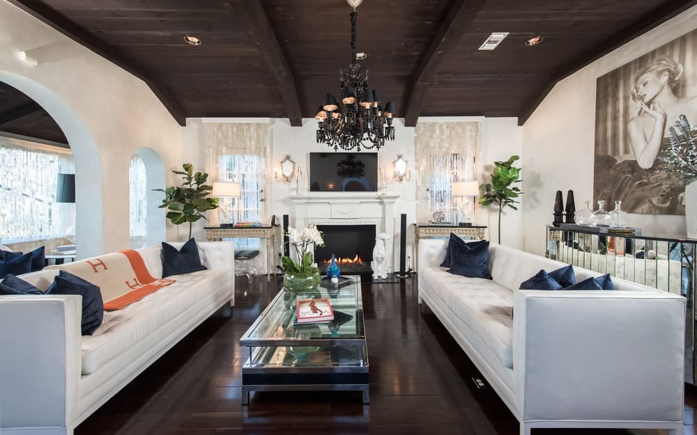 The living room of this house has a dark chandelier hanging over the glass-top coffee table across from the white fireplace topped with a wall-mounted TV. Images courtesy of Toptenrealestatedeals.com.