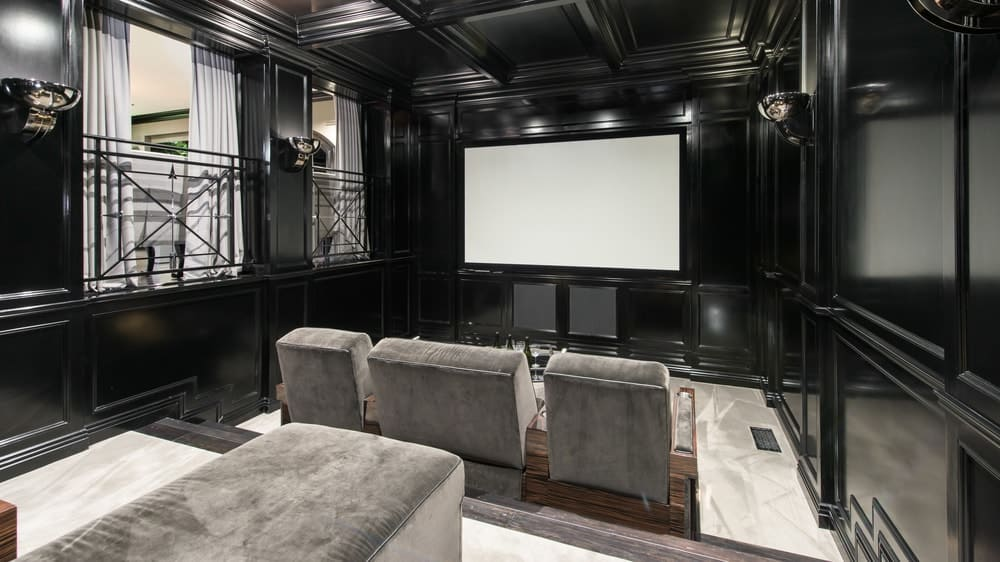 This home theater and media room has black walls and a black coffered ceiling with matching gray theater seats to bring the focus on the wide screen at the far end. Images courtesy of Toptenrealestatedeals.com.