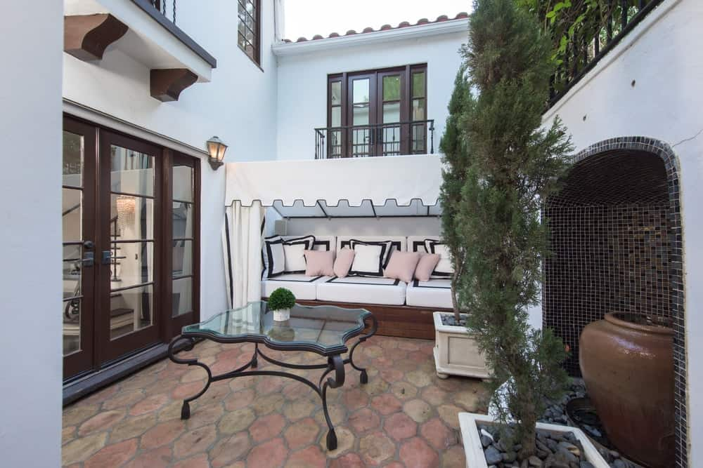 This lovely porch has terracotta flooring tiles that set an earthy background for white exterior walls matching with the linen tent of the built-in cushioned bench on the side of the glass doors. Images courtesy of Toptenrealestatedeals.com.