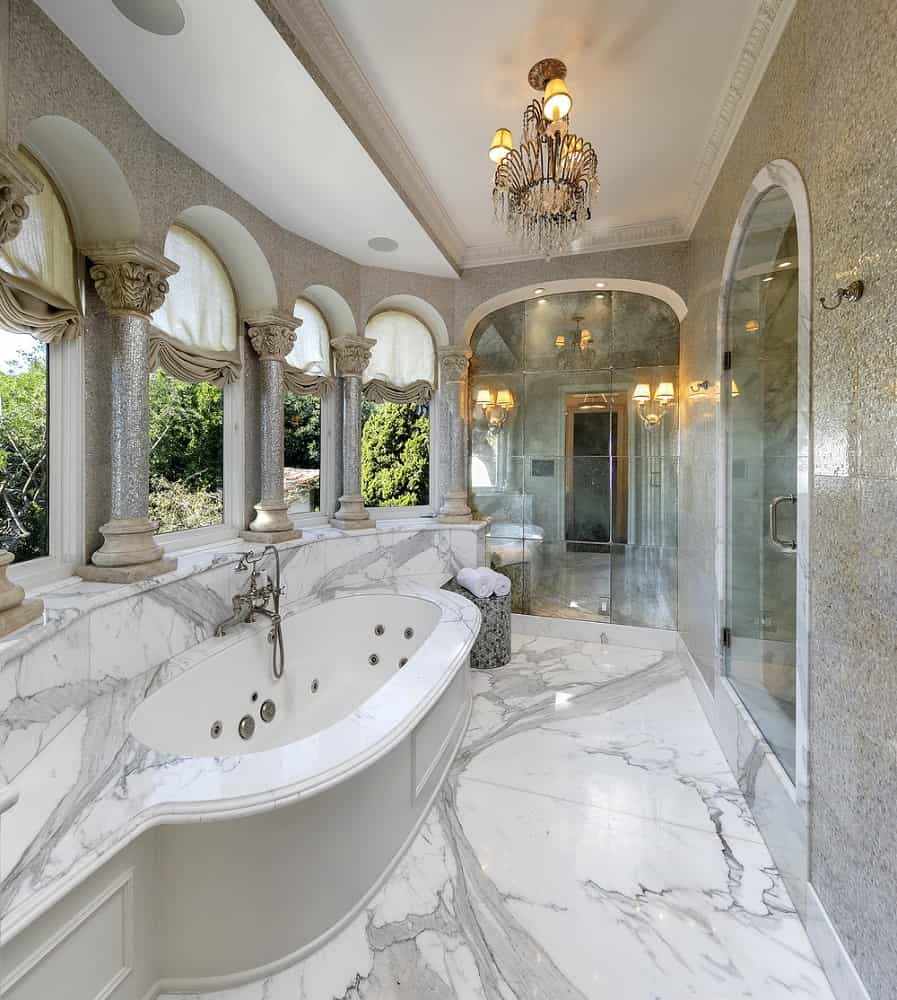 This is a luxurious bathroom with gorgeous white marble, a bathtub surrounded by multiple arches and glass enclosures complemented by golden details. Images courtesy of Toptenrealestatedeals.com.