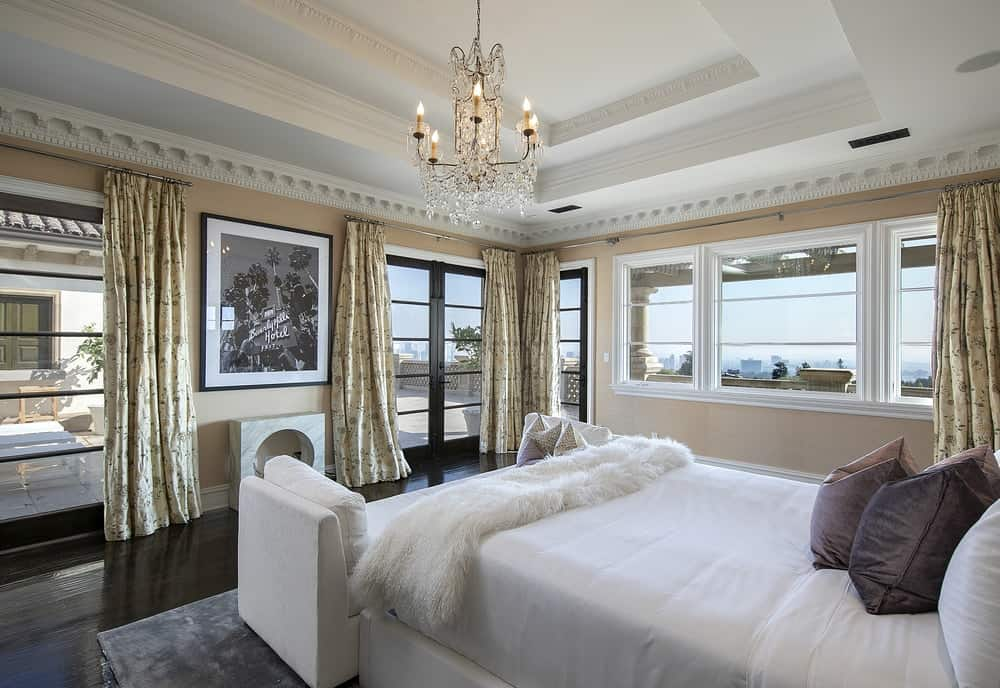 This bright airy bedroom has a charming golden chandelier hanging from its white tray ceiling brightened by the glass windows and glass door. Images courtesy of Toptenrealestatedeals.com.