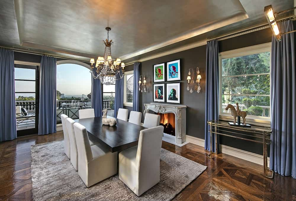 The formal dining area of the house has a large dark wooden dining table surrounded by beige upholstered dining chairs on an area rug covering the hardwood flooring. Images courtesy of Toptenrealestatedeals.com.