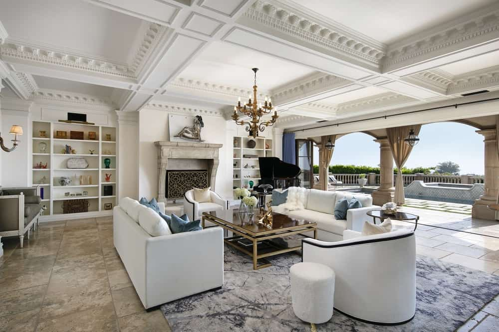 This luxurious large living room has an elegant white coffered ceiling that hangs a chandelier over the coffe table surrounded by a white sofa set that are warmed by the large fireplace. Images courtesy of Toptenrealestatedeals.com.