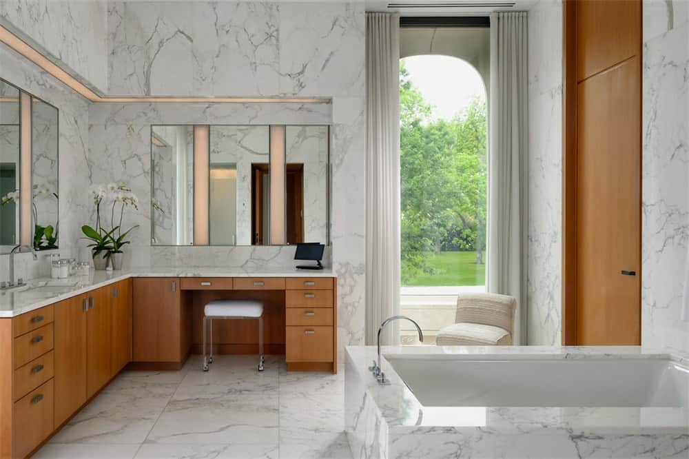 This is a large bathroom with white marble floor extending to the housing of the large bathtub and the walls of the L-shaped vanity with wooden cabinetry. Images courtesy of Toptenrealestatedeals.com.
