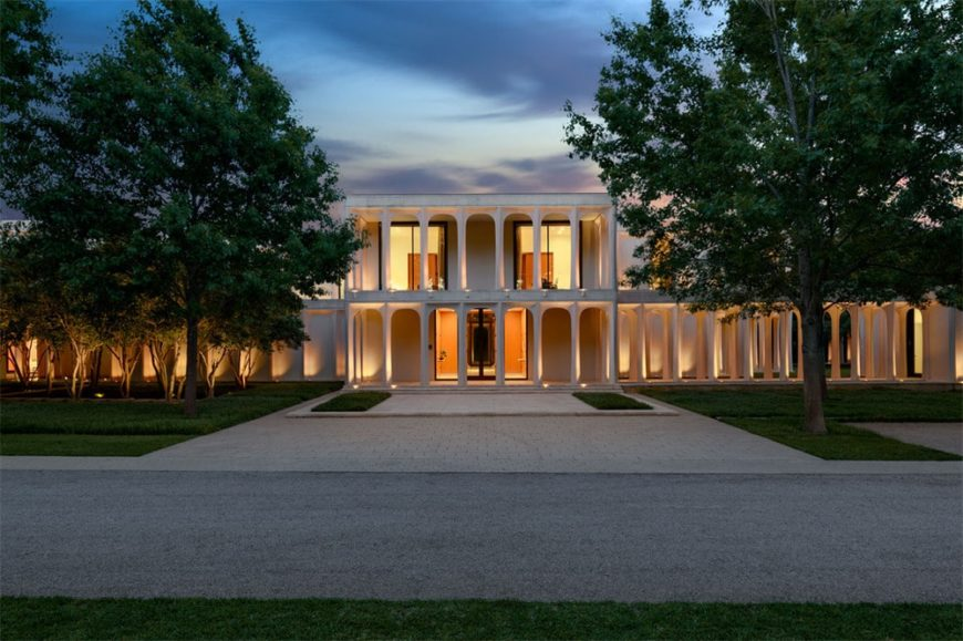This gorgeous mansion glows warmly with the bright yellow lights coming from the interiors. This makes the thin pillars and arches of the exteriors stand out complemented by the tall trees of the front lawn with a large driveway in the middle. Images courtesy of Toptenrealestatedeals.com.