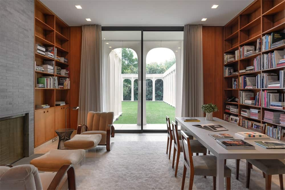 This library has a pair of tall bookshelves built into the walls flanking the large sliding glass door bringing in light to the couple of reading areas and the large table. Images courtesy of Toptenrealestatedeals.com.