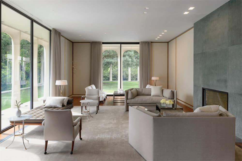 This living room has a spacious and comfortable feel to its various sitting areas and bright glass walls that illuminate the white ceiling and beige walls. Images courtesy of Toptenrealestatedeals.com.