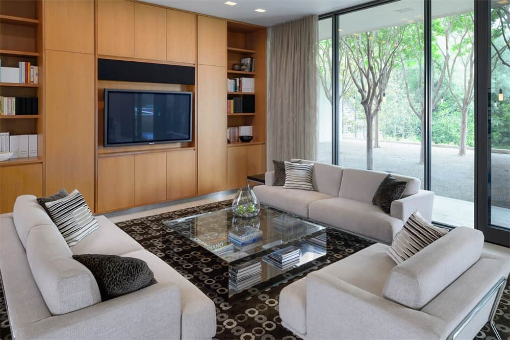 This other living room has enough space for three beige sofas surrounding a glass-top coffee table across from the large wooden structure that houses the TV. Images courtesy of Toptenrealestatedeals.com.