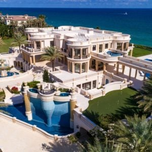This aerial view of the palace-like mansion shows its lovely beige exteriors filled with various arches and columns with wonderful complements of surrounding tall tropical trees, pools, large fountain and the gorgeous scenic blue ocean that is just a few steps from the backyard. Images courtesy of Toptenrealestatedeals.com.