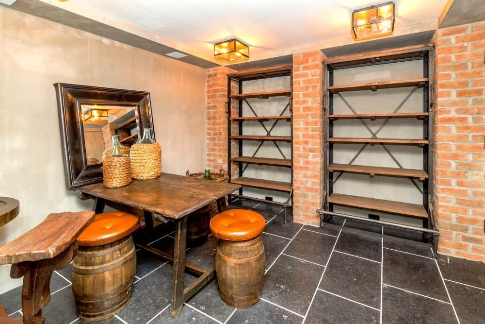 A basement with a small rectangular table paired with barrel seats, along with a wooden bar table and stool. Images courtesy of Toptenrealestatedeals.com.