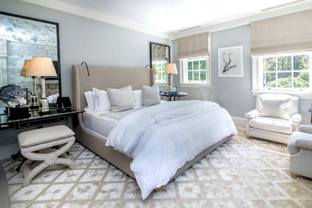 This bedroom suite offers a large modern luxurious bed set with a makeup table and chair set on the side, lighted by a table lamp. Images courtesy of Toptenrealestatedeals.com.