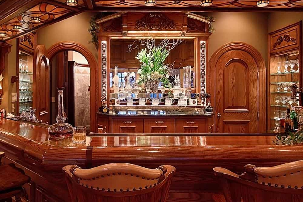 The large bar looks like it was originally a part of a five-star hotel with its rich wooden elements and cushioned stools. Images courtesy of Toptenrealestatedeals.com.