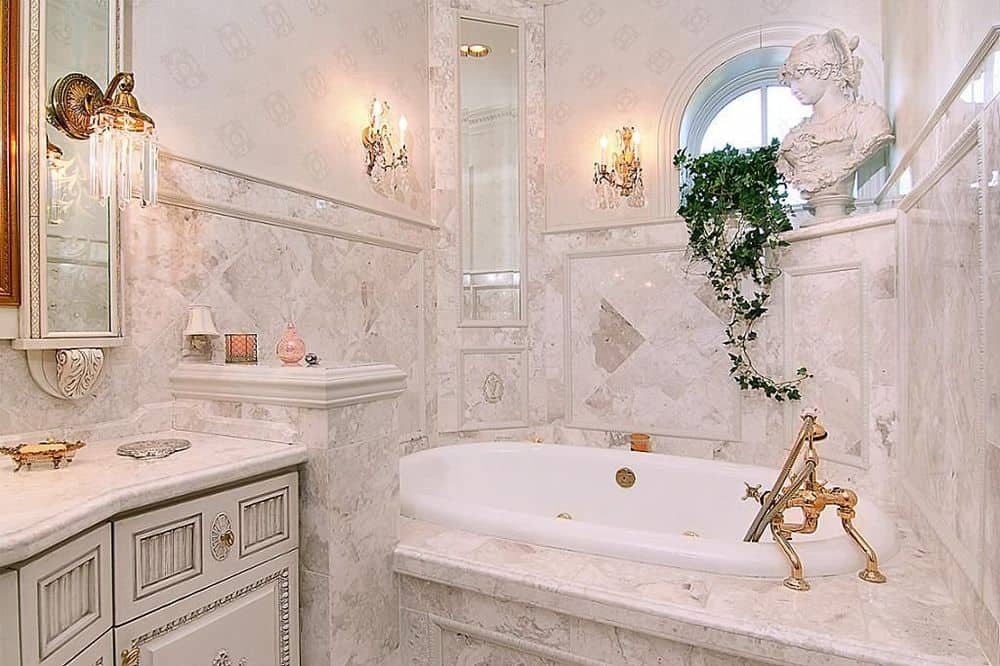 This is a more intimate bathroom with a bathtub inlaid on the corner with the same marble material as the backsplash and divider of the vanity area. The walls are also adorned with elegant wall-mounted lamps and a circular window above the bathtub. Images courtesy of Toptenrealestatedeals.com.