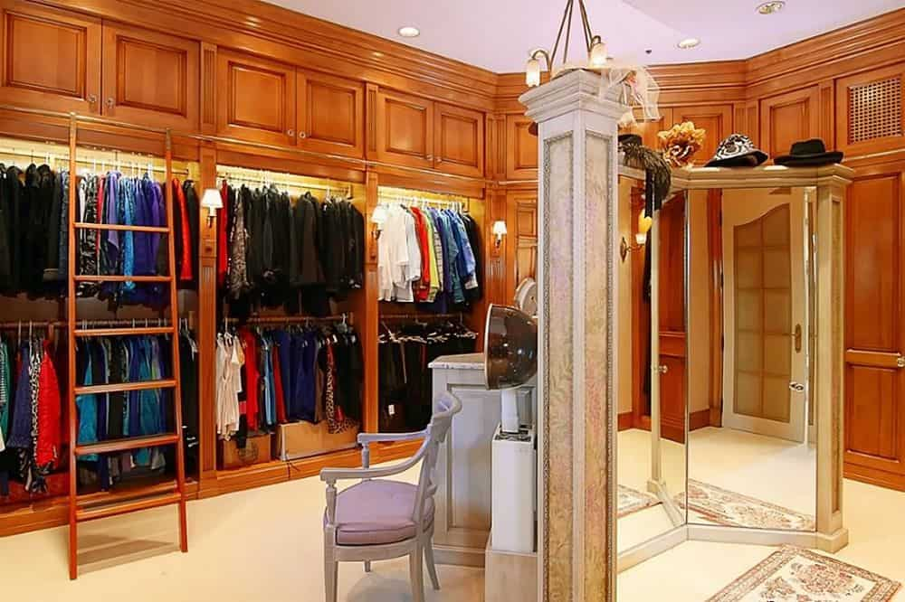 The spacious walk-in closet has large wooden structures dominating the walls with racks, cabinets and dreawers. The middle of the beige floor is adorned with a pillar supporting the full-sized mirror. Images courtesy of Toptenrealestatedeals.com.