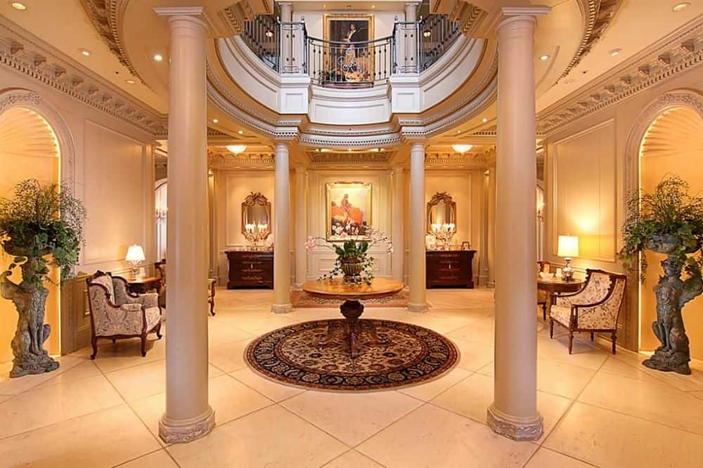 Upon entry of the mansion, you are welcomed by this grand foyer with a couple of beige pillars and a round wooden table in the middle underneath the circular indoor balcony above. Images courtesy of Toptenrealestatedeals.com.