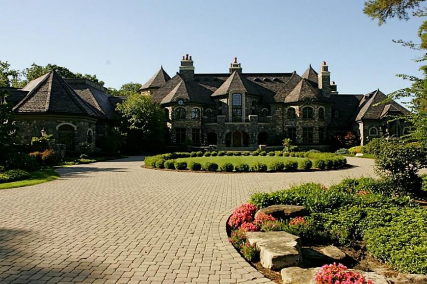 This is the front view of the mansion that boasts of Amish craftsmanship with its earthy exteriors complemented by the lovely foreground of the landscaping that has a stone brick driveway and walkways surrounded by flowering shrubs, grass and tall trees. Images courtesy of Toptenrealestatedeals.com.