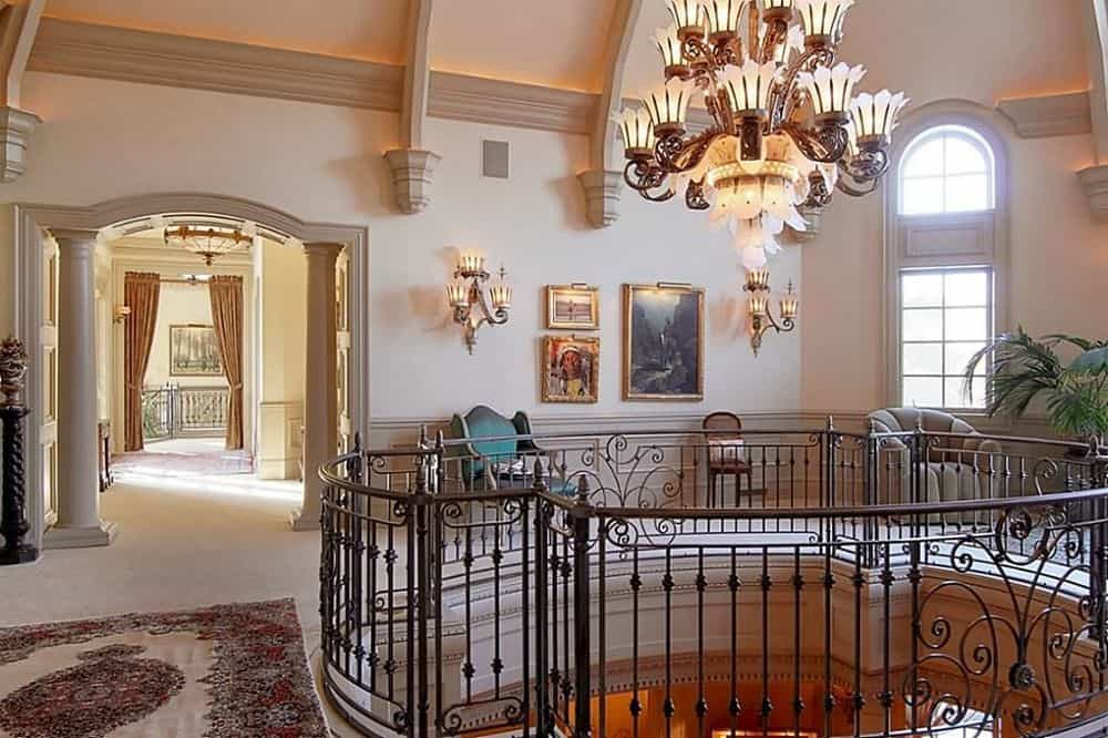 This is the indoor balcony with intricate wrought iron railings and a large majestic chandelier hanging in the middle that matches well with the wall-mounted lamps. Images courtesy of Toptenrealestatedeals.com.