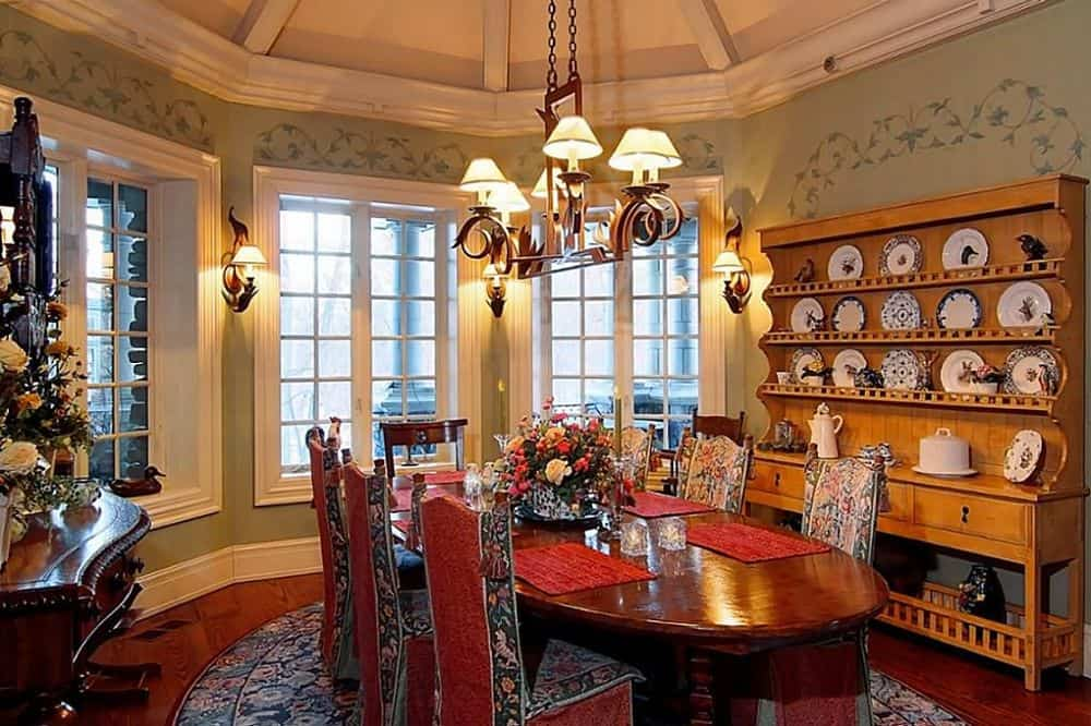 This is the informal dining area with a more intimate elliptical wooden dining table topped with a regal chandelier and surrounded wooden chairs with red cushions to match the area rug. Images courtesy of Toptenrealestatedeals.com.
