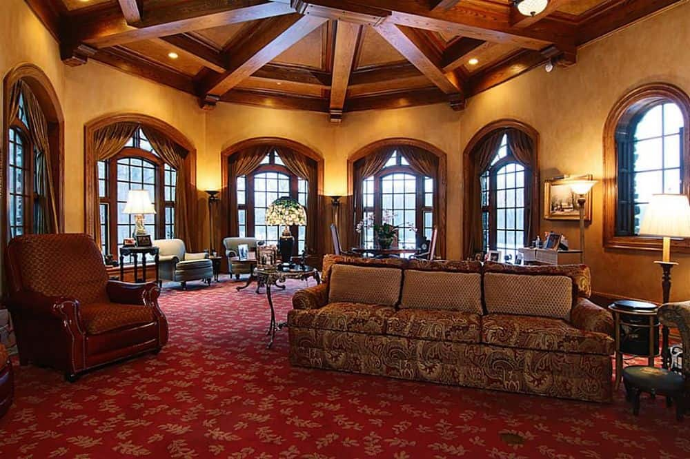 At the upper floor is a den with a tall wooden ceiling with exposed beams paired with large arched windows and carpeted flooring that elevates the various sitting areas and living room. Images courtesy of Toptenrealestatedeals.com.