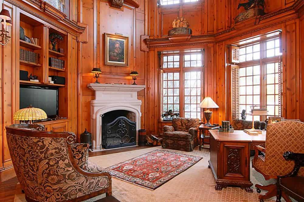 This angle of the office and library showcases a beautiful fireplace with a stone mantle that stands out against the rich and luxurious tall wooden walls with tall windows and transom windows to bring in natural lighting to balance the dark wooden walls. Images courtesy of Toptenrealestatedeals.com.