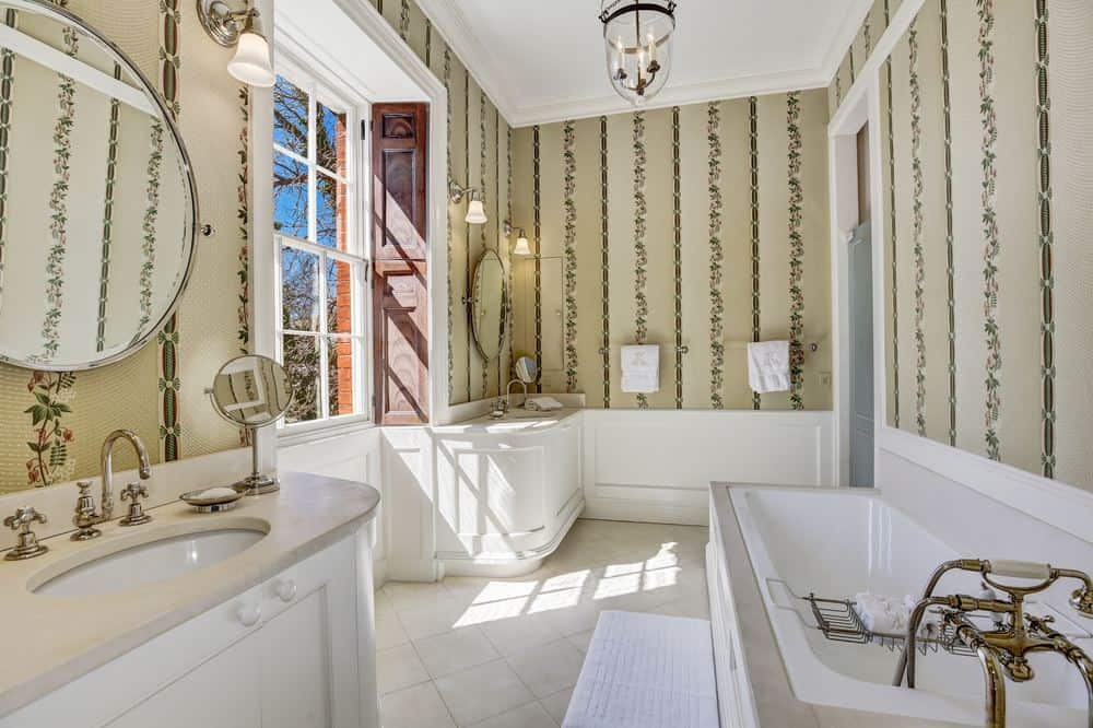 This bathroom has the same wallpaper as the bedroom. This makes the white porcelain sinks and bathtub stand out with the illumination of the abundance of natural lighting coming in from the large window. Images courtesy of Toptenrealestatedeals.com.