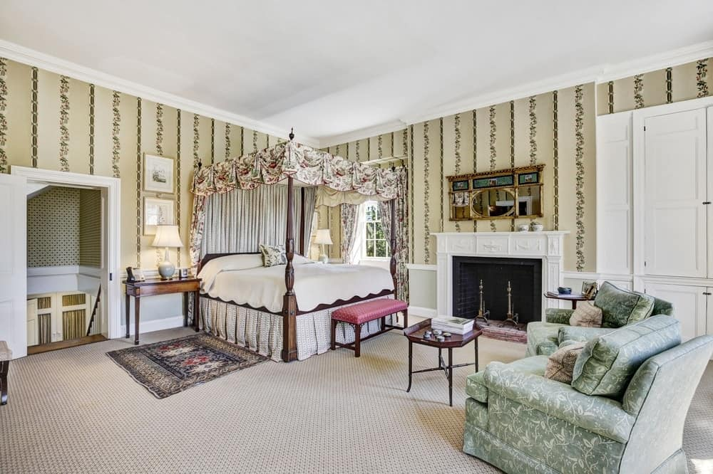 This bedroom has charming patterned beige wallpaper that matches well with the four-poster bed's curtains. There is also a fireplace with a white mantle that stands out beside the bed. Images courtesy of Toptenrealestatedeals.com.