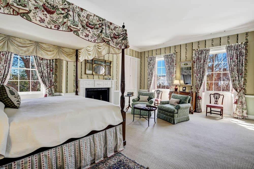 This angle shows more of the sitting area at the foot of the bed with a couple of green cushioned arm chairs by the curtained windows. Images courtesy of Toptenrealestatedeals.com.