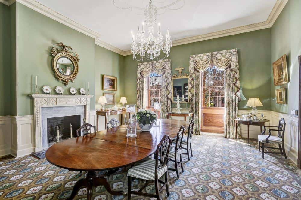 This formal dining area has gorgeous green walls that complements the wooden dining table, bright ceiling and the fireplace that gives the room warmth. Images courtesy of Toptenrealestatedeals.com.