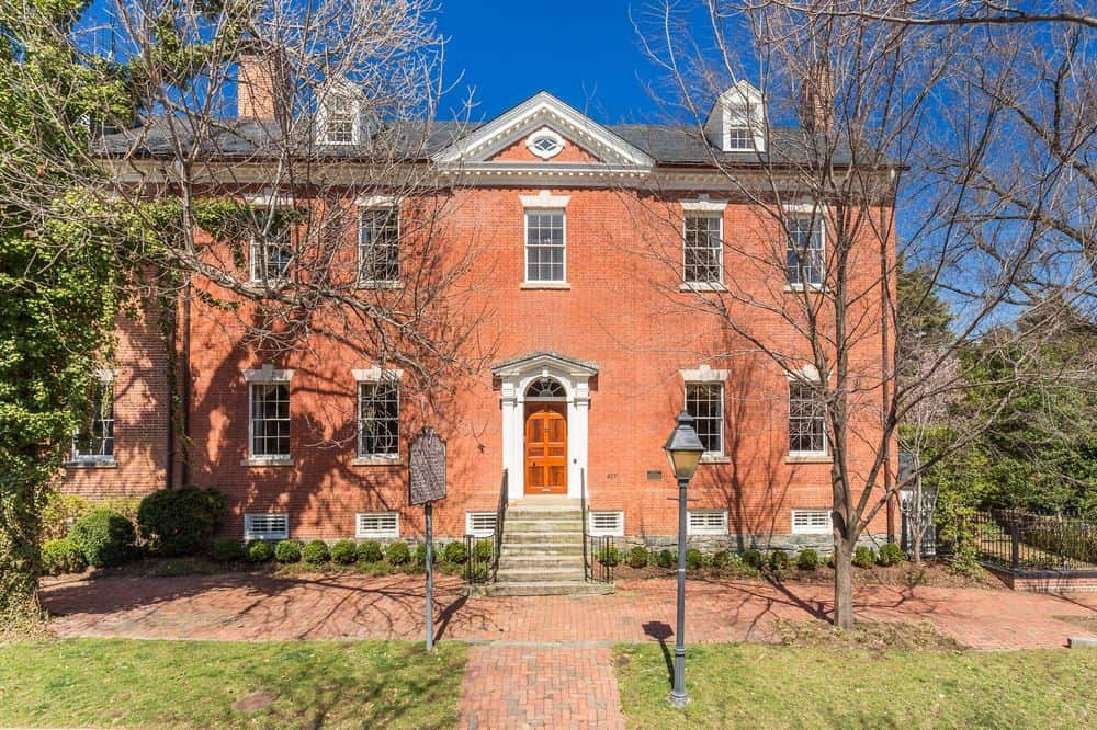 This is the front view of the house that features the tall trees flanking the main entry. There is also a terracotta sidewalk and small lawns of grass in the front of the house. Images courtesy of Toptenrealestatedeals.com.