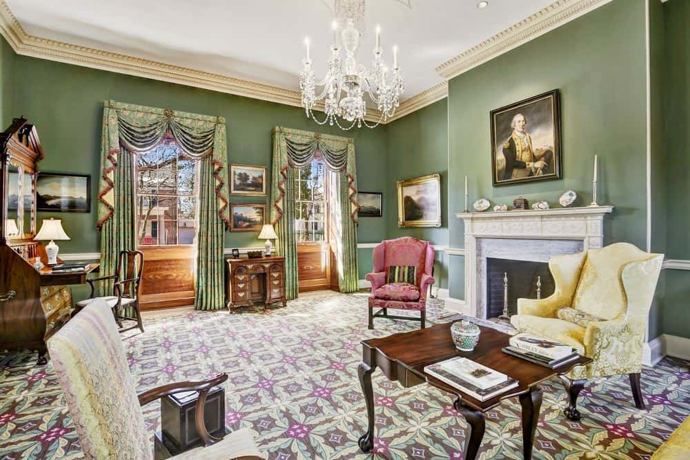 This living room has a patterned carpeted flooring paired with lovely green walls that contrast the bright ceiling and the mantle of the fireplace. Images courtesy of Toptenrealestatedeals.com.