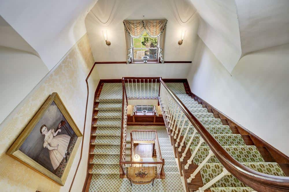 This is the view of the staircase from the second floor landing. There you can see the gorgeous classic paintings that adorn the beige walls of the staircase that has wooden banisters and green carpeting. Images courtesy of Toptenrealestatedeals.com.