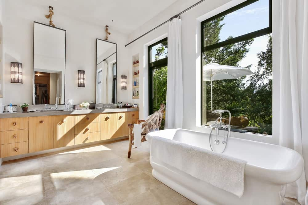 The bathroom has a simple setup of wooden vanity and freestanding bathtub by the windows. These are augmented by the beautiful treetop scenery afforded by the wide glass windows. Images courtesy of Toptenrealestatedeals.com.