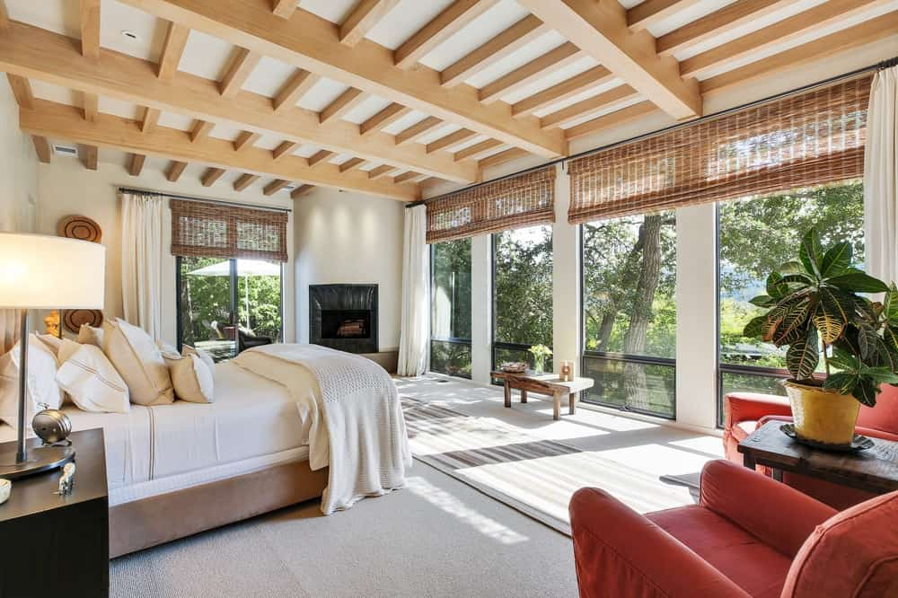 The primary bedroom is brightened by surrounding glass walls shaded with rustic woven wicker shades that match with the tall ceiling filled with exposed wooden beams. These are all then warmed by the fireplace in the corner. Images courtesy of Toptenrealestatedeals.com.