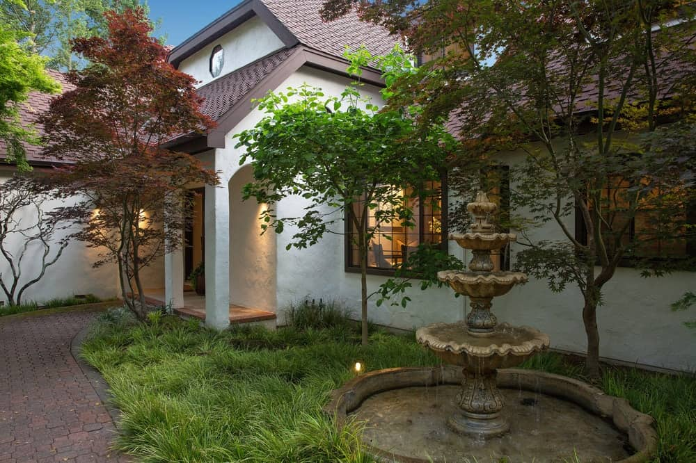 The beautiful main entry of the house is adorned with a stone fountain on the side surrounded by various trees and grass giving the house a rustic foreground. Images courtesy of Toptenrealestatedeals.com.