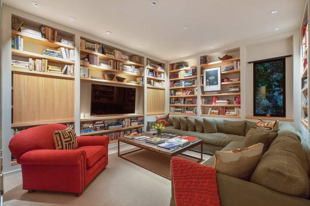 The family room and media room of the house has built-in wooden structures on its walls that has shelves and houses the mounted TV paired with a large L-shaped sectional sofa. Images courtesy of Toptenrealestatedeals.com.