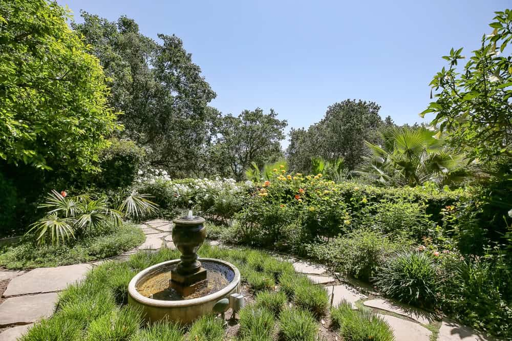 In the middle of the large garden is a quaint fountain surrounded by decorative shrubbery adding character to the lush greenery of the landscape. Images courtesy of Toptenrealestatedeals.com.