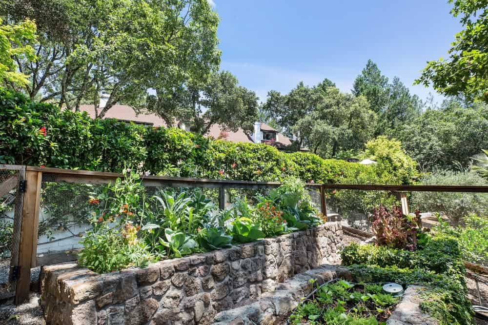 The house is perfectly paired with a surrounding landscape that is filled with rustic stone planters filled with various shrubs, herbs and vegetables. Images courtesy of Toptenrealestatedeals.com.