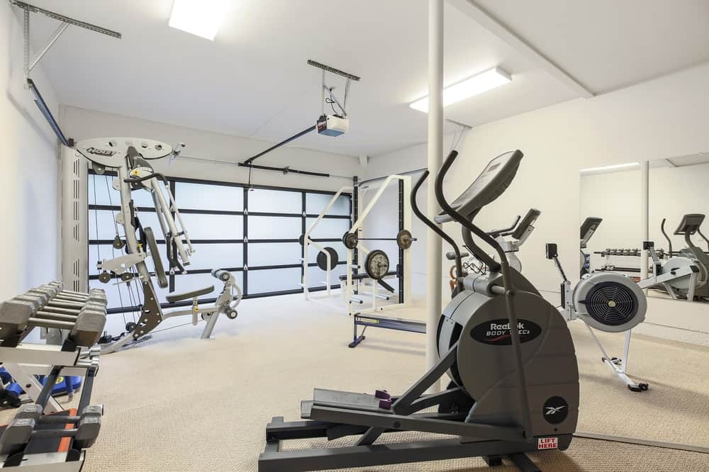 The exercise room and gym has the latest state-of-the-art equipment with a simple white background to its walls, ceiling and floor along with frosted glass to its roll-up garage door. Images courtesy of Toptenrealestatedeals.com.