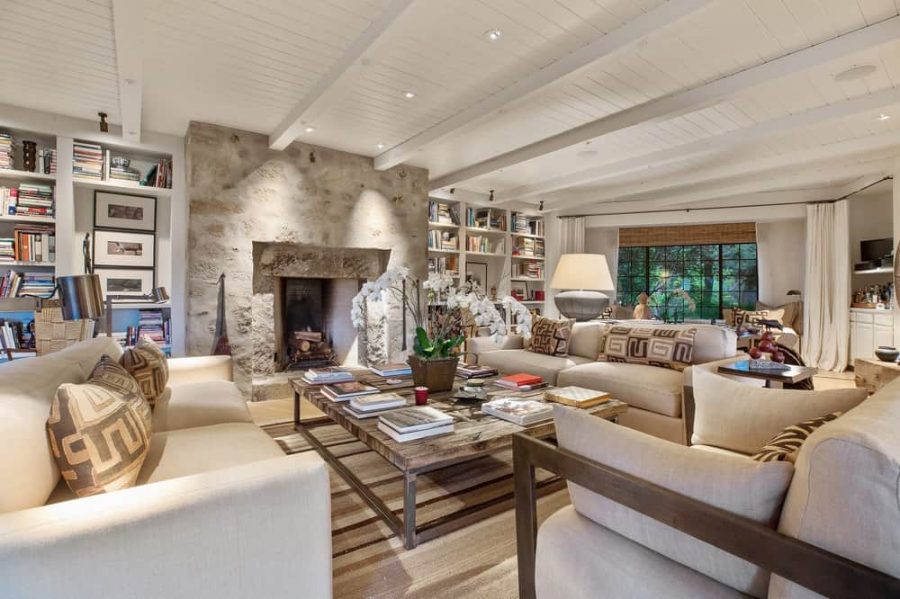 The beautiful living room has a large stone fireplace that reaches to the white ceiling with exposed beams. This matches with the light beige sofa set and light hardwood flooring. Images courtesy of Toptenrealestatedeals.com.