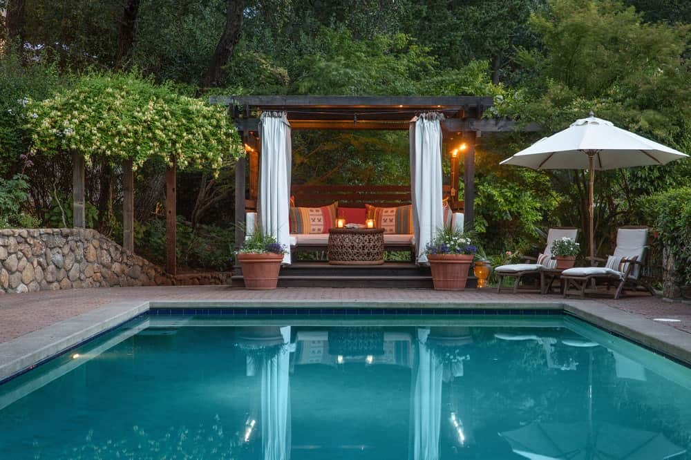 This is a closer look at the pool side area and its two comfortable sitting areas. One is built into the cabana with cushions and curtains and beside it are lawn chairs facing the pool under a large umbrella. Images courtesy of Toptenrealestatedeals.com.