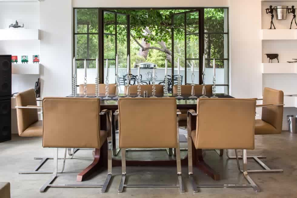 The charming dining area just a few steps from the living room has modern stainless steel chairs upholstered with brown leather surrounding the wooden dining table on an Industrial-style concrete flooring. Images courtesy of Toptenrealestatedeals.com.