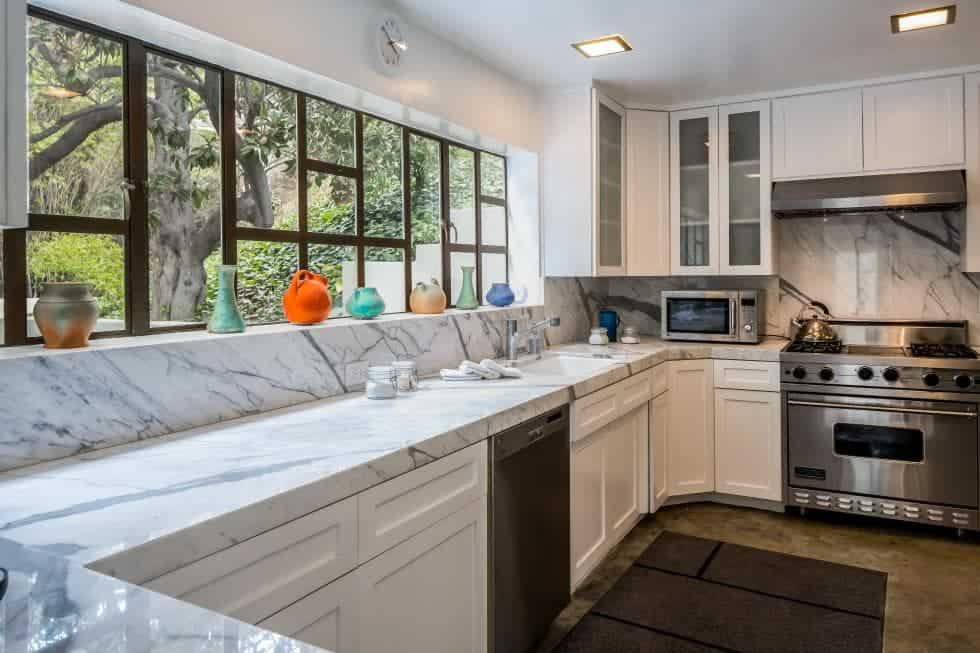 This is the U-shaped kitchen of the house with lovely white marble countertops and a wide window offering a view of the garden outside. Images courtesy of Toptenrealestatedeals.com.