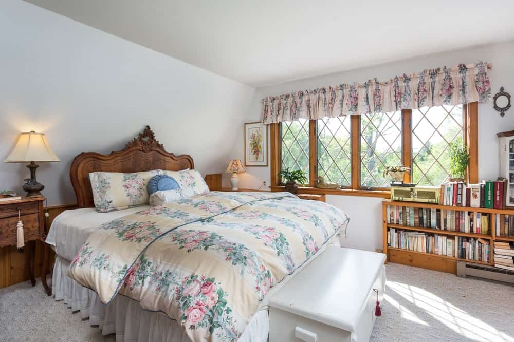 This bedroom has a large comfortable bed with a wooden headboard adorned with carvings. The floral patterns of the bed sheets and pillows matches with the curtains of the row of windows with wooden frames. Images courtesy of Toptenrealestatedeals.com.