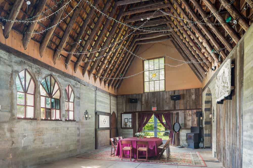 This is the interior of the repurposed barn with a tall wooden cove ceiling that has exposed wooden beams. This is where the dining area is placed making the red table cloth stand out in the middle of the stone flooring. Images courtesy of Toptenrealestatedeals.com.