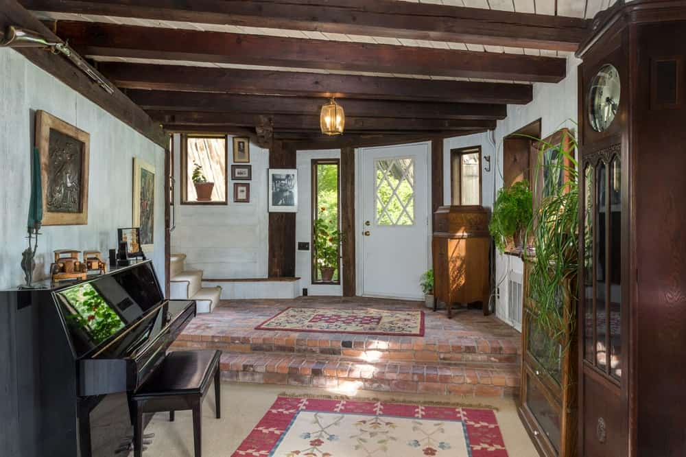 Upon entry of the house, you are welcomed by the charming and rustic foyer with terracotta flooring tiles and exposed wooden beams to its ceiling. Images courtesy of Toptenrealestatedeals.com.