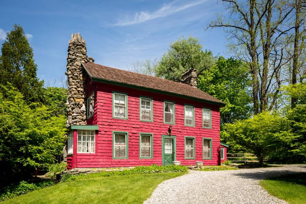 This house has vibrant and textured red exterior walls that are complemented by the tall stone chimney on the side of the house. Its red tone makes it stand out against the lush green landscaping. Images courtesy of Toptenrealestatedeals.com.