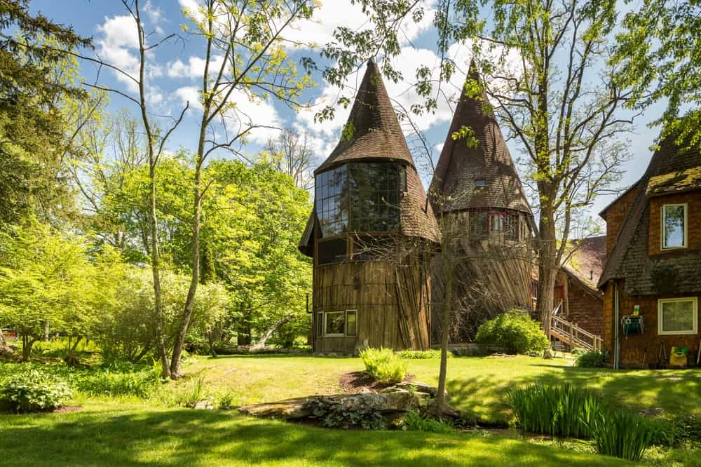 The towers of the studio looks like they come from a fairy tale with their earthy exteriors and pointed rooftops that stand out against the surrounding lush landscape of trees and shrubs. Images courtesy of Toptenrealestatedeals.com.