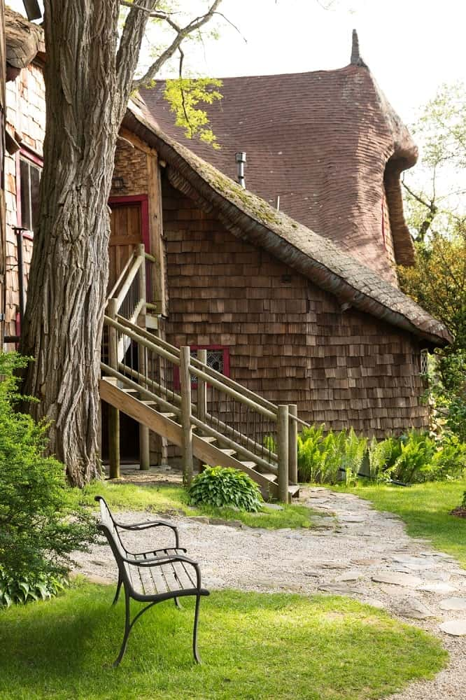 Outside the fantastical studio and its earthy thatched materials is a charming spot fitted with a park bench to better enjoy the lovely scenery of the landscape. Images courtesy of Toptenrealestatedeals.com.