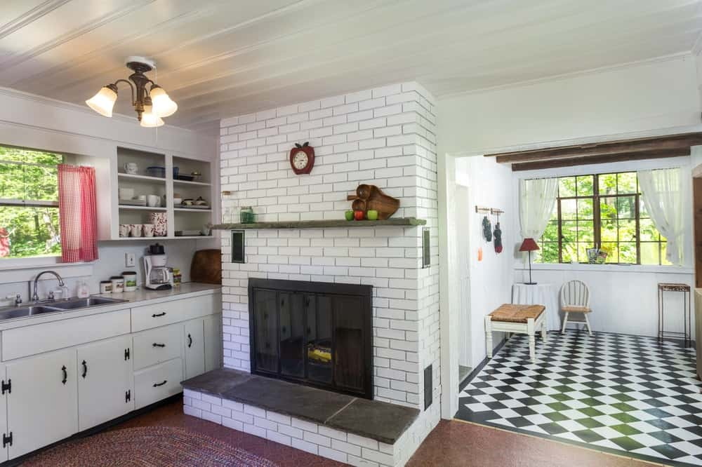 The kitchen has a charming white shiplap ceiling to pair with the white cabinetry and white bricks of the fireplace. Images courtesy of Toptenrealestatedeals.com.