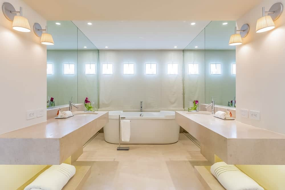 This bathroom has charming light pink stone floating vanities flanking the walkway to the freestanding bathtub on the far wall. Images courtesy of Toptenrealestatedeals.com.